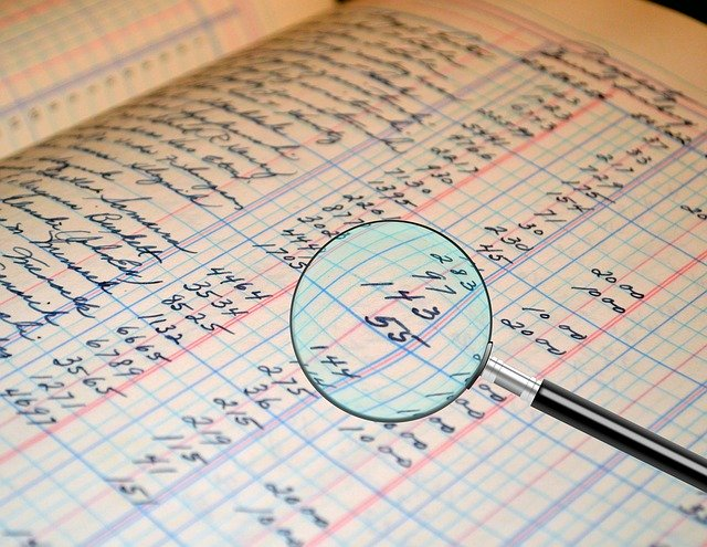 magnifying glass over accounting ledger