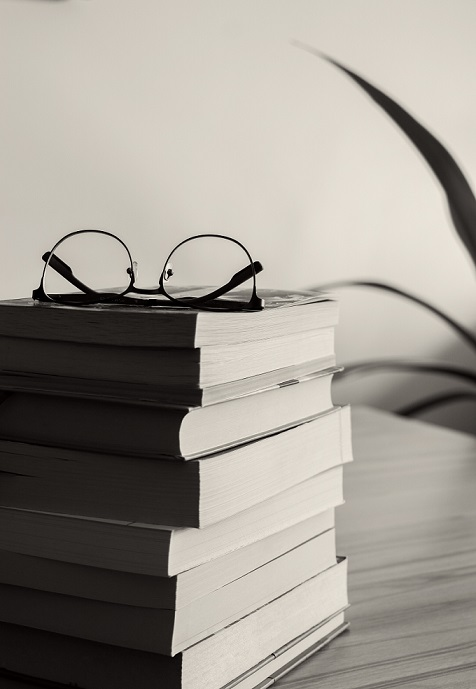 a stack of books near a plant and a pair of glasses on top