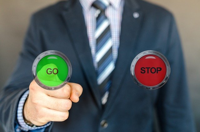 a man in a business suit, pressing a 'go' button instead of 'stop'.