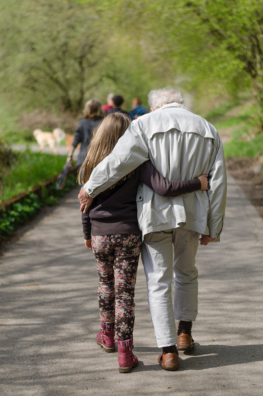 granddaughter with arm wrapped around her grandfather walking along a path.