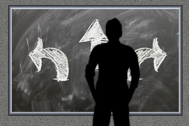 silhouette of man staring at a blackboard with three different directional arrows