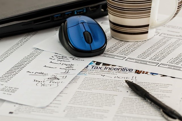 scattered tax forms on a desk with a computer mouse, coffee cup and pen