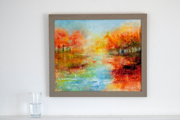 a landscape painting of autumn on a lake with a glass of water near the frame
