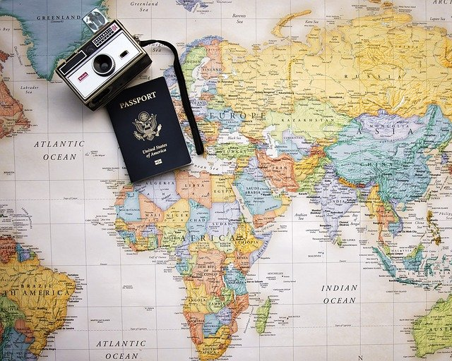 passport and camera on top of a world map