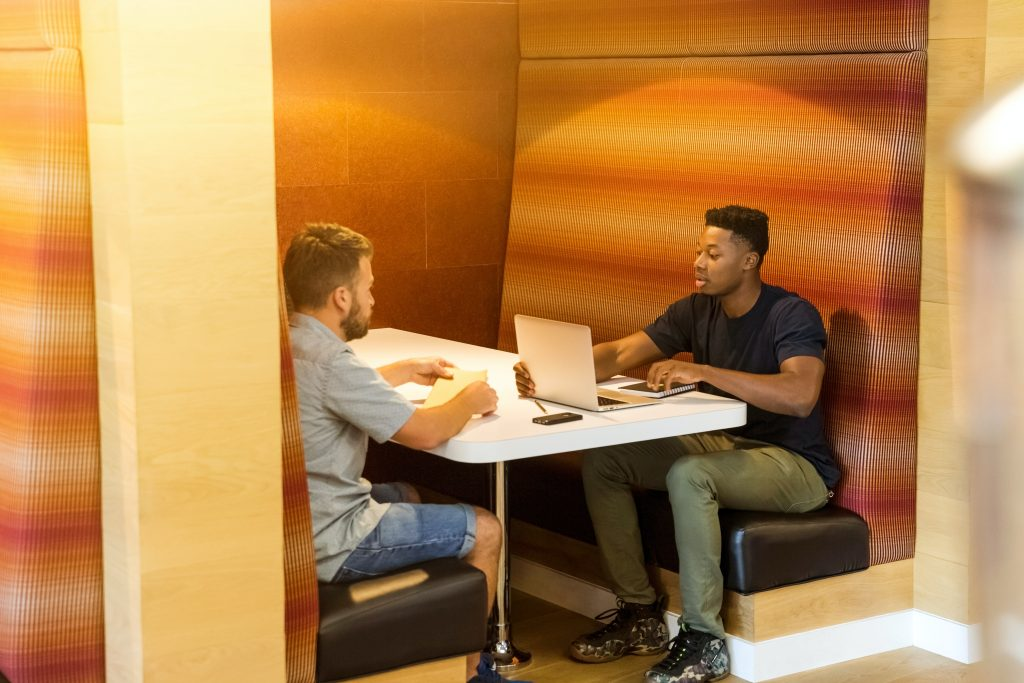 two entrepreneurs sitting at a table with laptop open