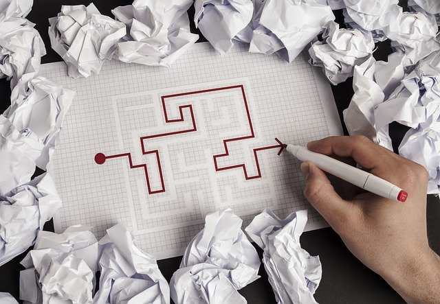 hand drawing through a maze surrounded by crumpled paper