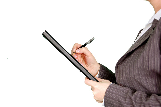 woman signing a document on a clipboard