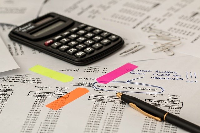 calculator and pen atop a stack of unorganized papers with highlights and circles around the tax implication