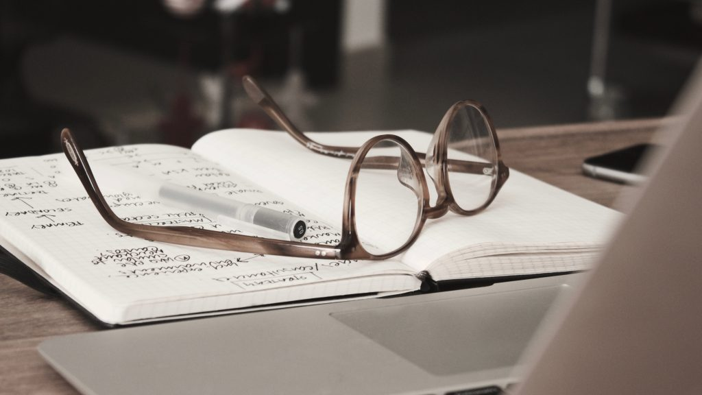 a pair of glasses resting atop an open journal with notes