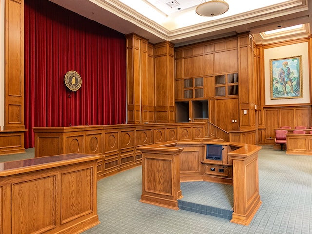 a wide view of an empty court room with wooden benches and witness stands and a red curtain